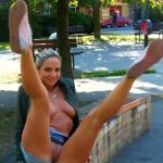 Legs high up and a landing strip blonde on park bench
