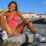 Katya Clover sitting on rock pantieless