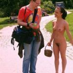Naked brunette with basket talking with tourist