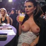 Luxury brunette drinking cocktail and flashing perfect round breasts
