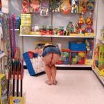 Pantyless in toy shop: Blonde in denim skirt bent over