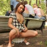 Redhead flashing behind some teens in park
