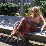 Smiling blonde with huge breasts topless on bench