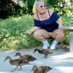 justbuttcat: Feeding ducklings in a park.
