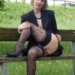 Middle aged amateur woman in black stockings flashes her mature cunt outdoors