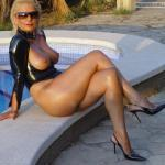 Busty MILF with pierced nipples sitting at the pool in sexy latex outfit and stilettos