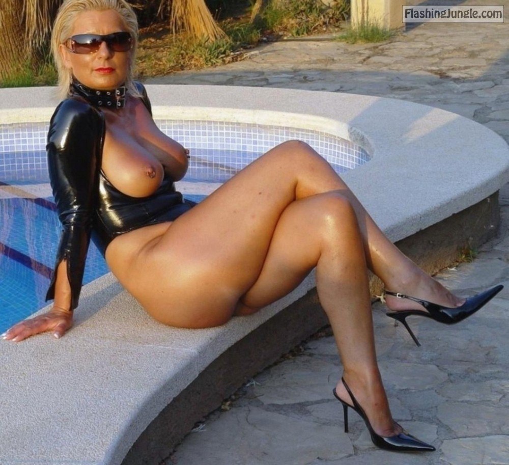 Busty MILF with pierced nipples sitting at the pool in sexy latex outfit and stilettos public flashing no panties milf pics mature boobs flash bitch
