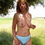 Wild mature woman exposes her saggy tits in the field