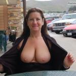 Charming mature lady opens up her blouse and shows big juggs on the street