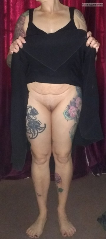Inked mature woman pulling up skirt and flashing bald cunt