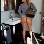 Blonde cougar showing off firm butt in public toilet