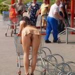 Famous brunette in beige skirt bent over shopping trolley pantieless upskirt