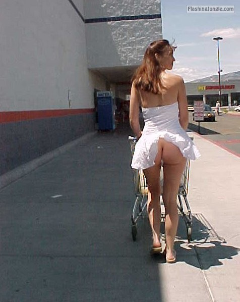No panties under white dress Outside a shop in a short dress and showing…