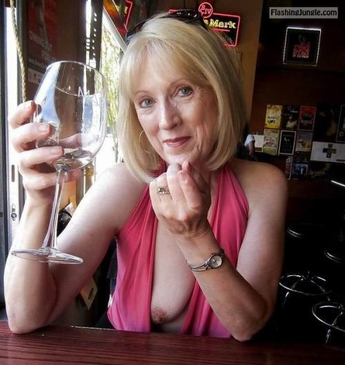 One mature boob out at restaurant – blond granny in red drinking wine