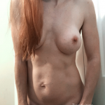 Skinny redhead MILF getting nude with a smile