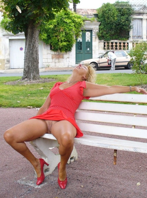 Pantyless cougar in red dress and heels on park bench upskirt pussy flash public flashing no panties milf pics mature bitch